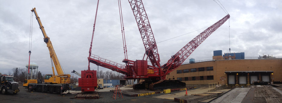 Red Crane Lifting a Load onto the Roof